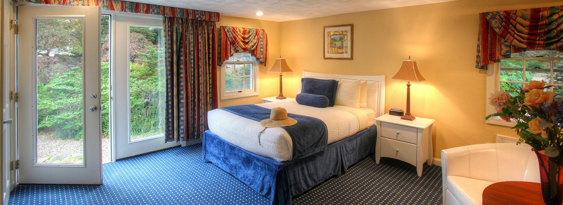Spacious hotel room with queen bed, large french doors and sitting chair next to table with vase of flowers