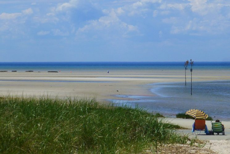 Expansive beach area near bright blue waters with two people sitting in beach chairs near green dune grass
