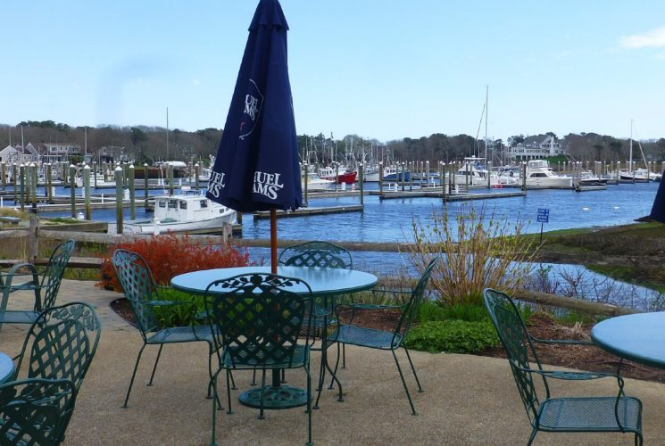 Outdoor patio dining area with green tables and chairs at waters edge with marina in background