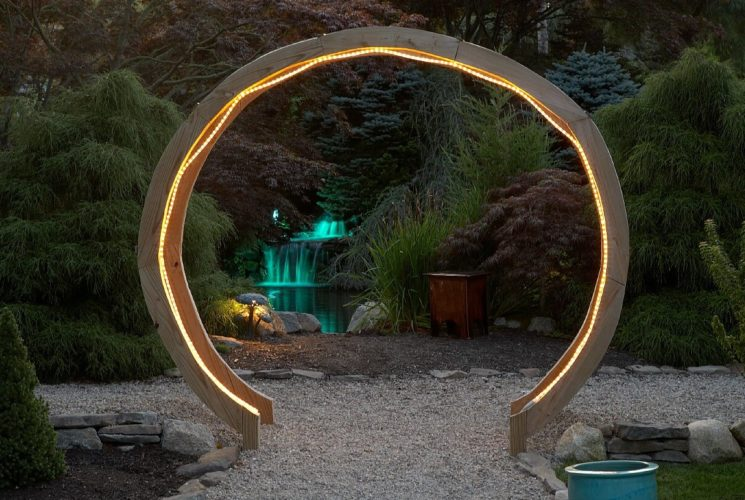 Large circular wooden gate with rope lights lit up at night with colorful green fountain in the background