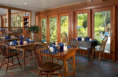 Large dining room with a wall of windows and four tables for two set for breakfast