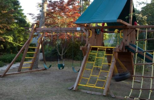 Outdoor wooden play structure for kids with rope ladders, slide and three swings