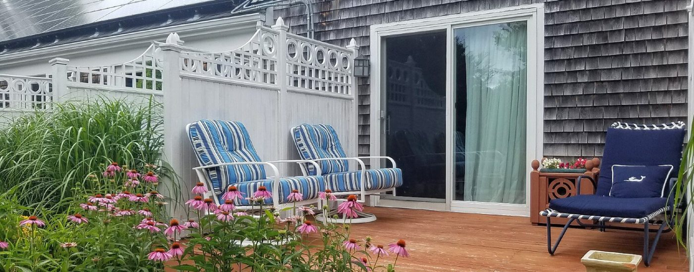 Deck with white privacy fence, sliding glass doors, cushioned sitting chairs and colorful plants and flowers