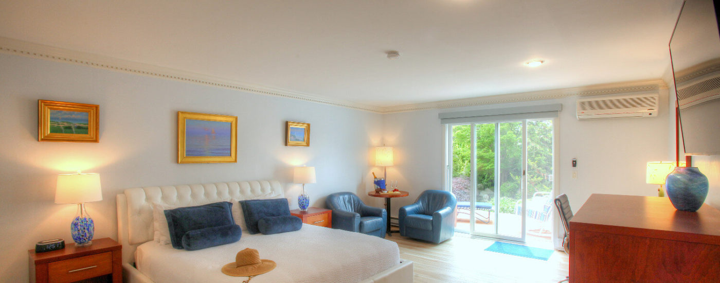 Spacious bedroom with king bed, blue carpet, two leather sitting chairs and slider door to outdoor deck