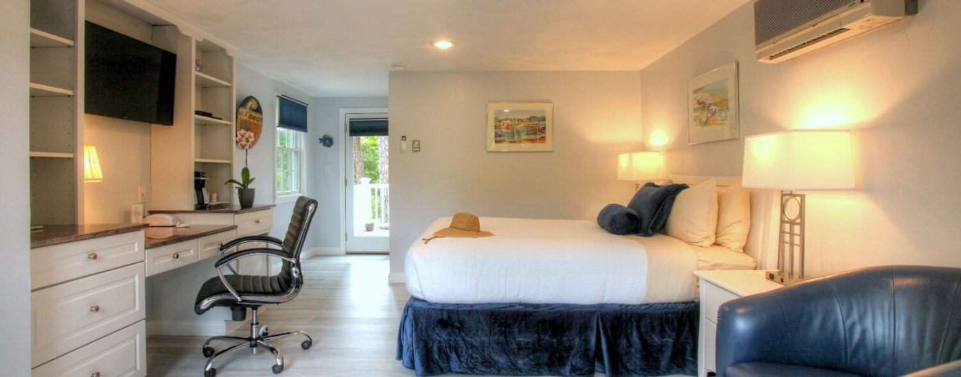 Bright guest room with queen bed, off white walls, light grey flooring, large windows blue leather chairs