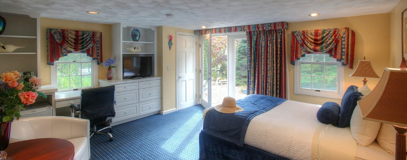 Spacious, bright bedroom with French doors, queen bed, sitting chair and table and hutch with writing desk and TV
