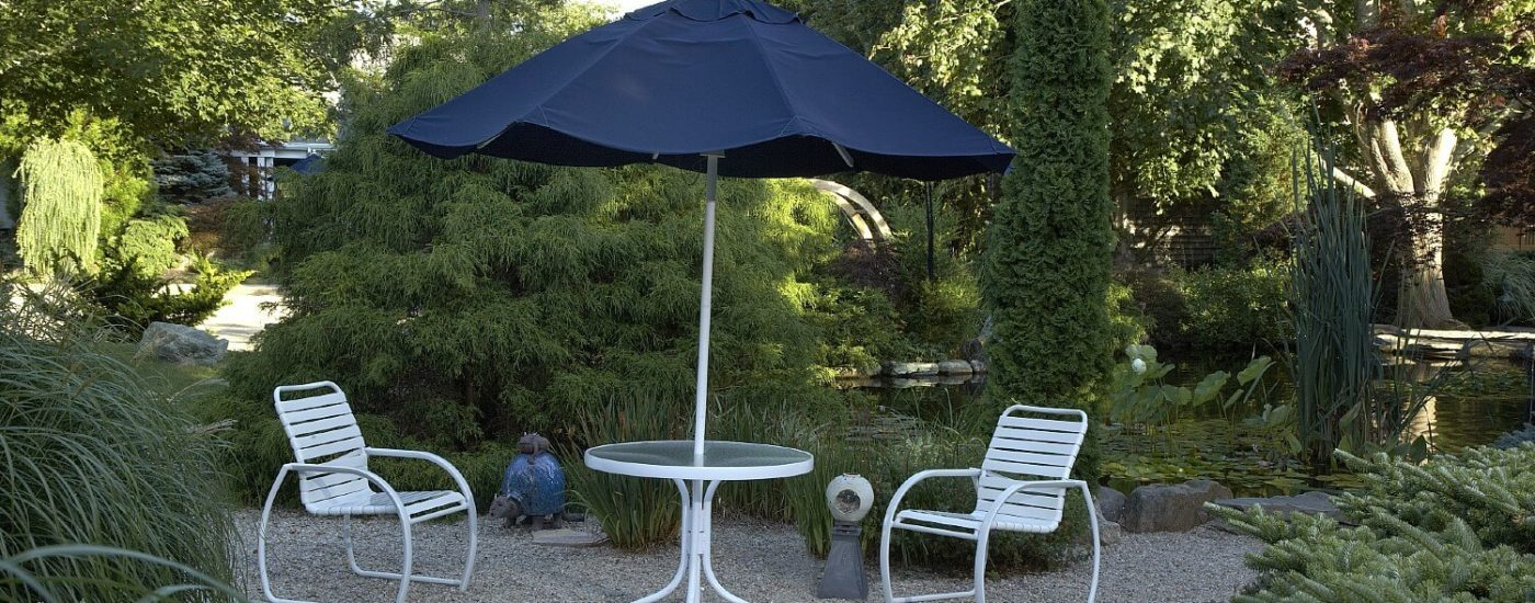 White outdoor patio table with two chairs and a blue umbrella on stone area surrounded by lush green trees and bushes