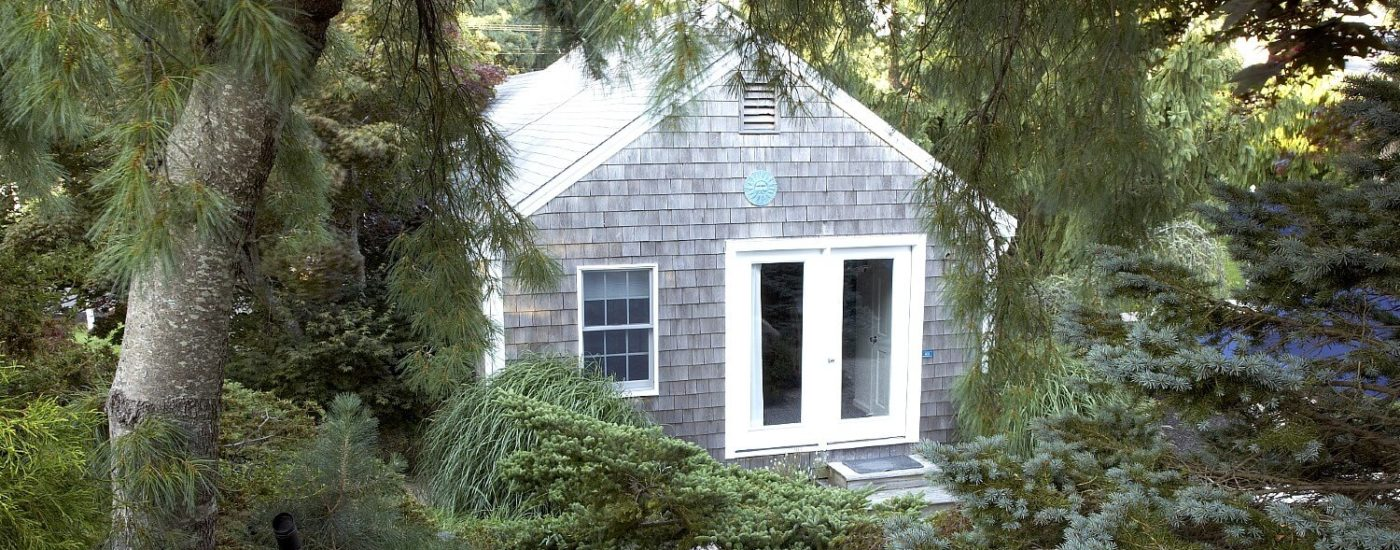 Small cottage with grey shingles and white trim nestled among tall trees and green shrubs