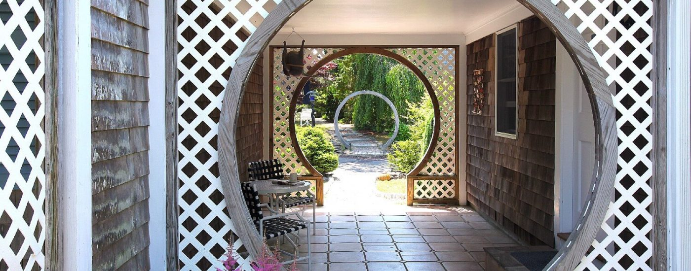 Breezeway with several circular arches along a path lined with trees and plants