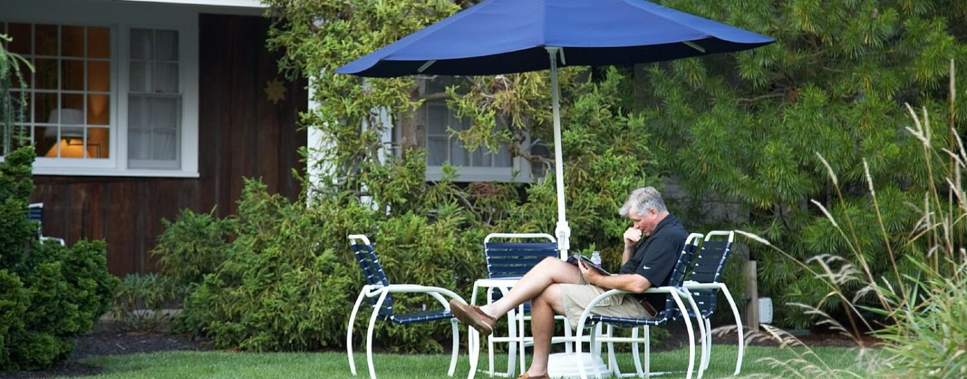 A man in shorts and a black shirt sitting at a white outdoor patio table with chairs and a blue umbrella on a lawn