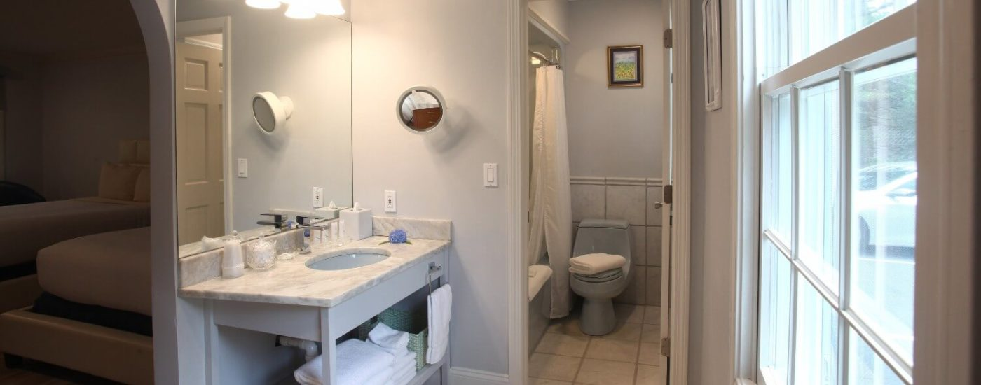 Circular porthole within a white fence looking into the outside patio of a a block of hotel rooms lined with chairs