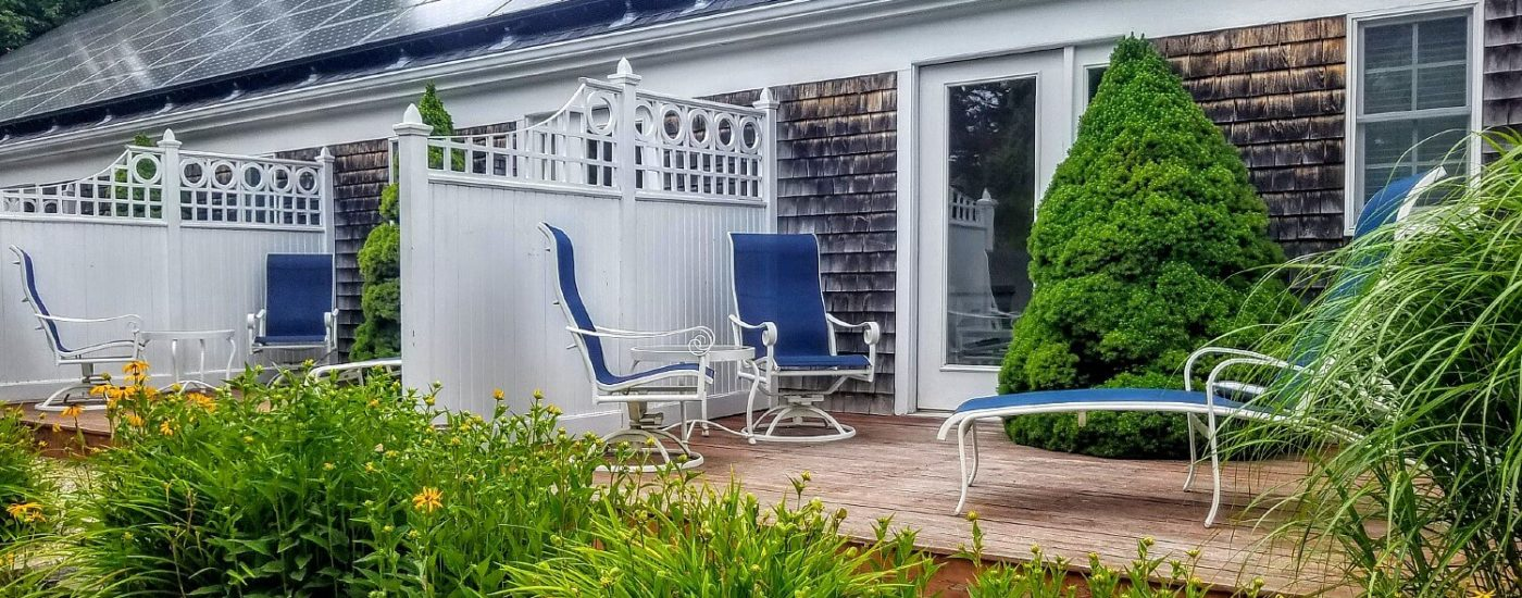 Outdoor decks separated by white privacy fences with sitting chairs and surrounded by lush green plants and shrubs