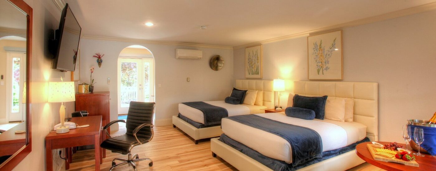 Spacious bedroom with two queen beds, leather sitting chairs, writing table and arched doorway leading
