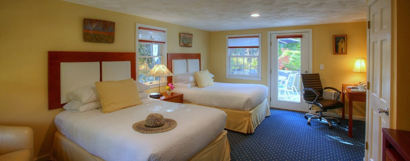 Large studio bedroom with two queen beds in white linens, bright windows and writing desk with lamp