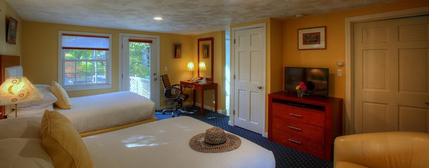 Spacious and bright bedroom with two queen beds, leather sitting chair, writing desk and dresser with TV