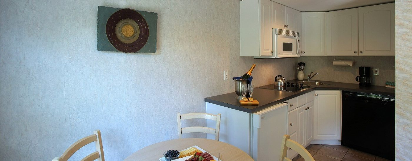 Kitchenette of a studio apartment with black countertop and white cabinets and round table with three chairs