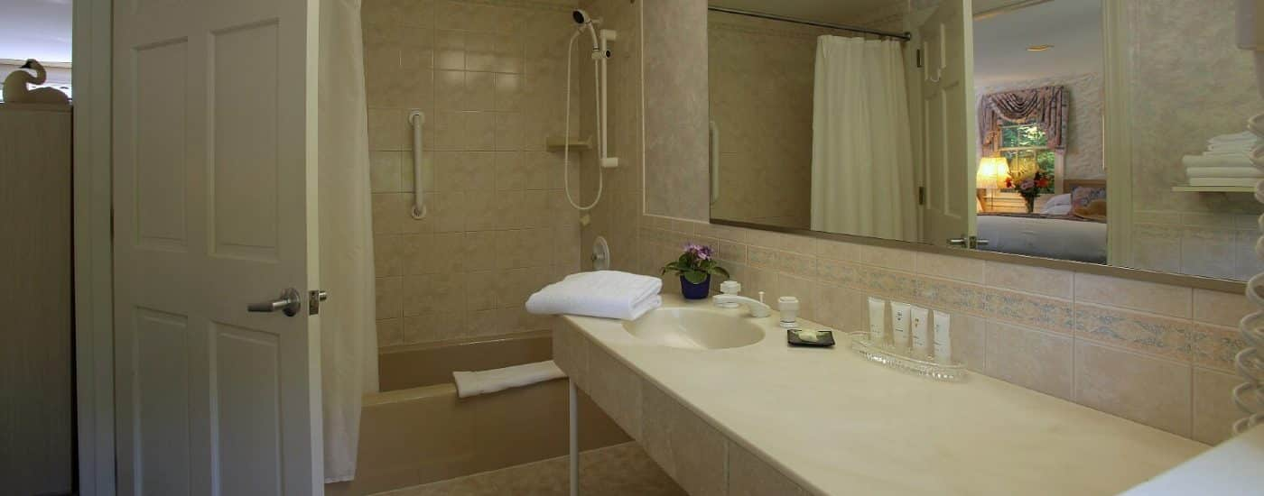 Bathroom with long cream single-sink countertop and bathtub with shower
