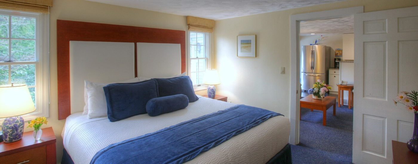 Bedroom with king bed, two bright windows and doorway leading into living area with coffee table and kitchenette