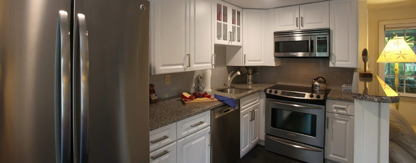 Small kitchen in a cottage with granite countertops, white cabinets and stainless steel appliances