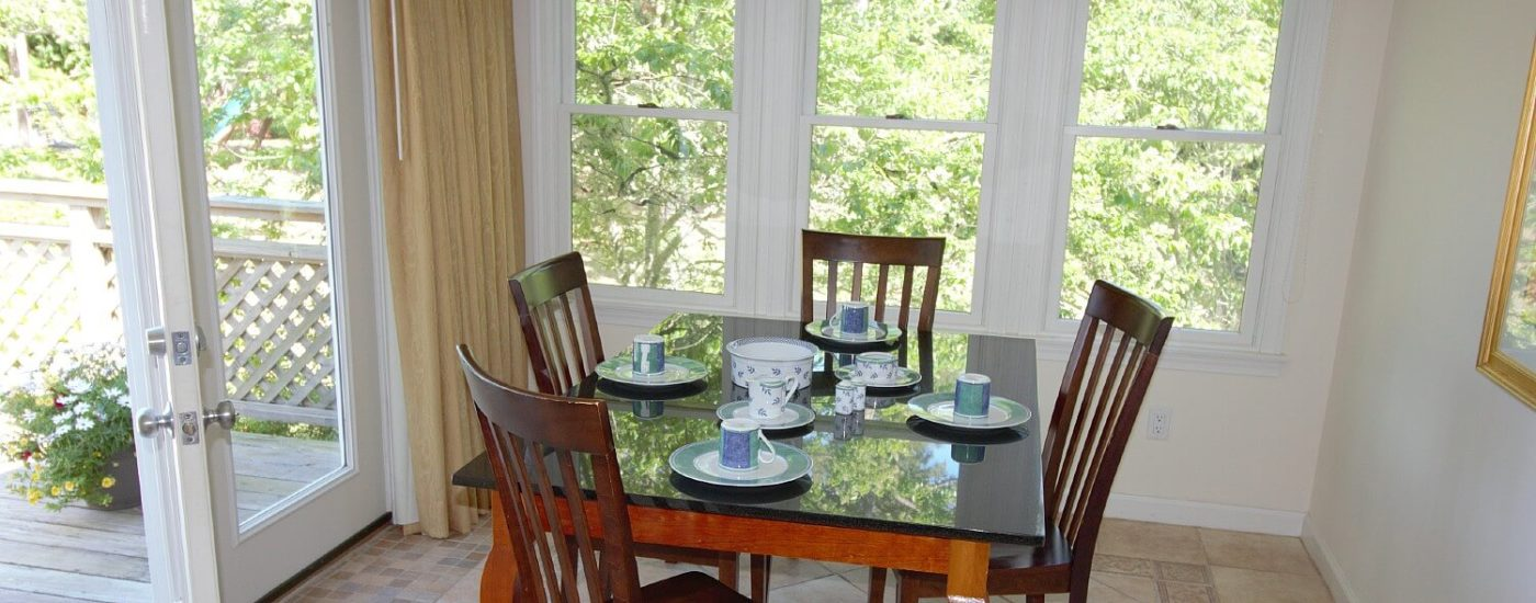 Small dining table set with four chairs in a room with bright windows and door open to a deck with flowers