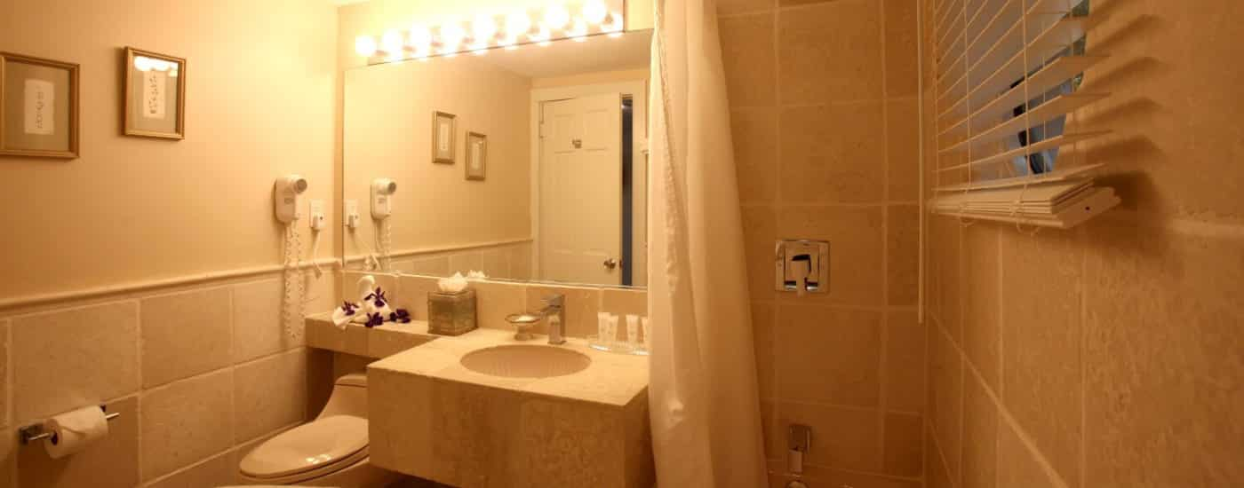 Beige bathroom with marble tiled wall around bathtub and window, tile sink with large mirror.