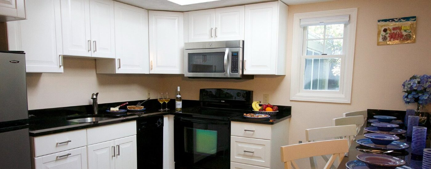 Kitchen with black countertop and white cabinets and bar counter with chairs set with four place settings