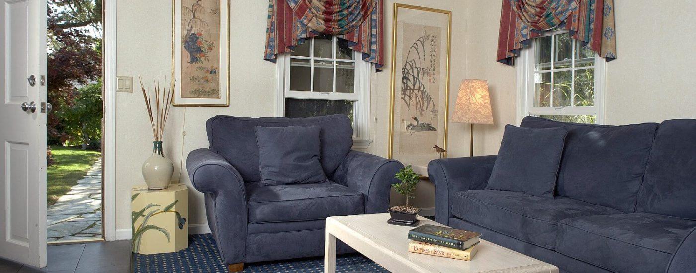 Sitting area of a cottage with blue couch and chair, coffee table and front door open to a stone sidewalk