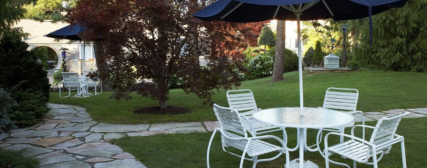 Spacious outdoor area with trees, bushes, stone sidewalks and white patio tables with four chairs and blue umbrellas