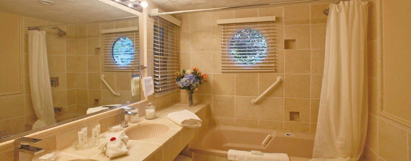 Bright light grey tiled bathroom, bathtub , double vanity sink with large wall mirror& toilet.