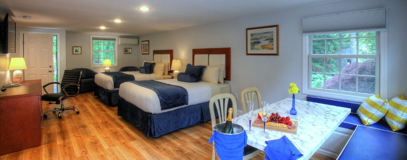 Large studio lodging featuring two queen beds, dinette by large windows and writing desk under TV on the wall
