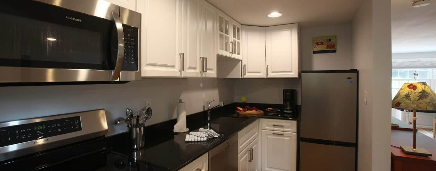Kitchen area of a studio apartment with black countertops, white cabinets and stainless steel appliances