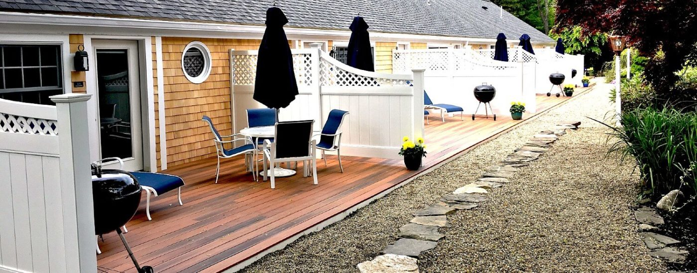 A row of studio apartments with private back patios, each with a bbq and patio table with umbrella