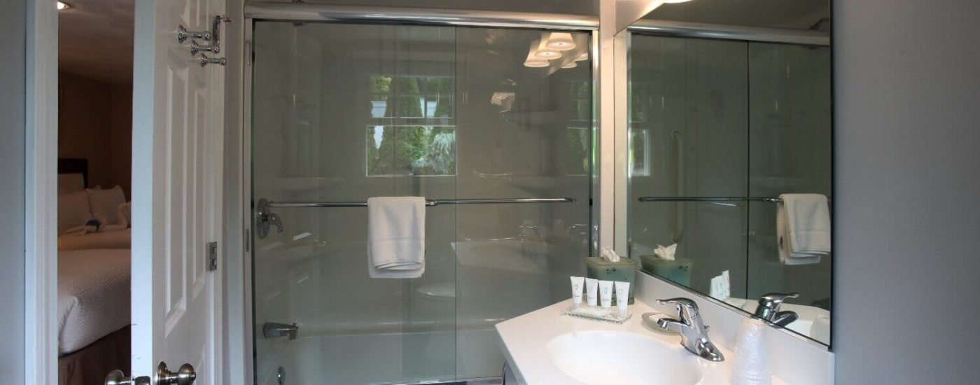 Bathroom with single vanity and large mirror, tub and shower with glass doors