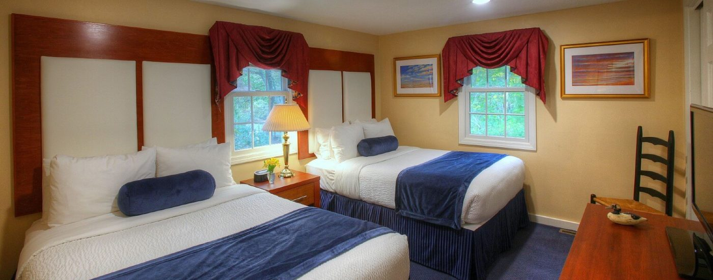 Cottage bedroom with two queen beds in white and blue linens, two windows and dresser with TV