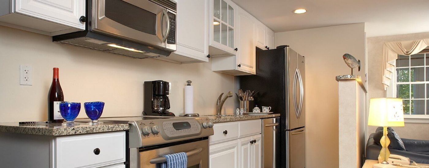 Kitchenette of a cottage with granite countertops, white cabinets and stainless steel appliances