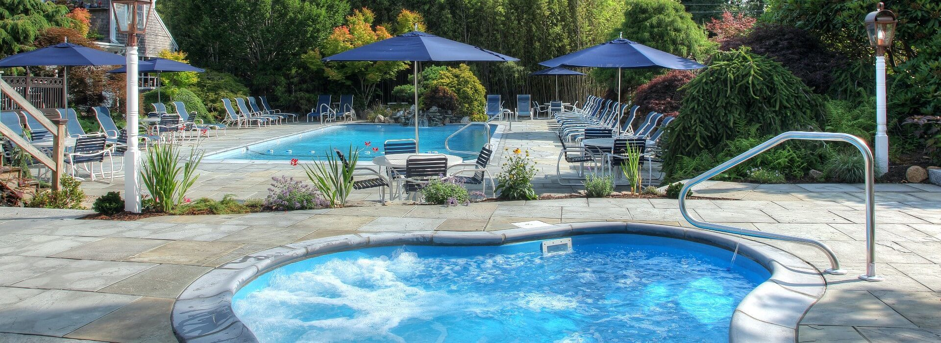 Large outdoor patio with pool lined with sunning chairs, a hot tub with bubbling water and patio tables with blue umbrellas