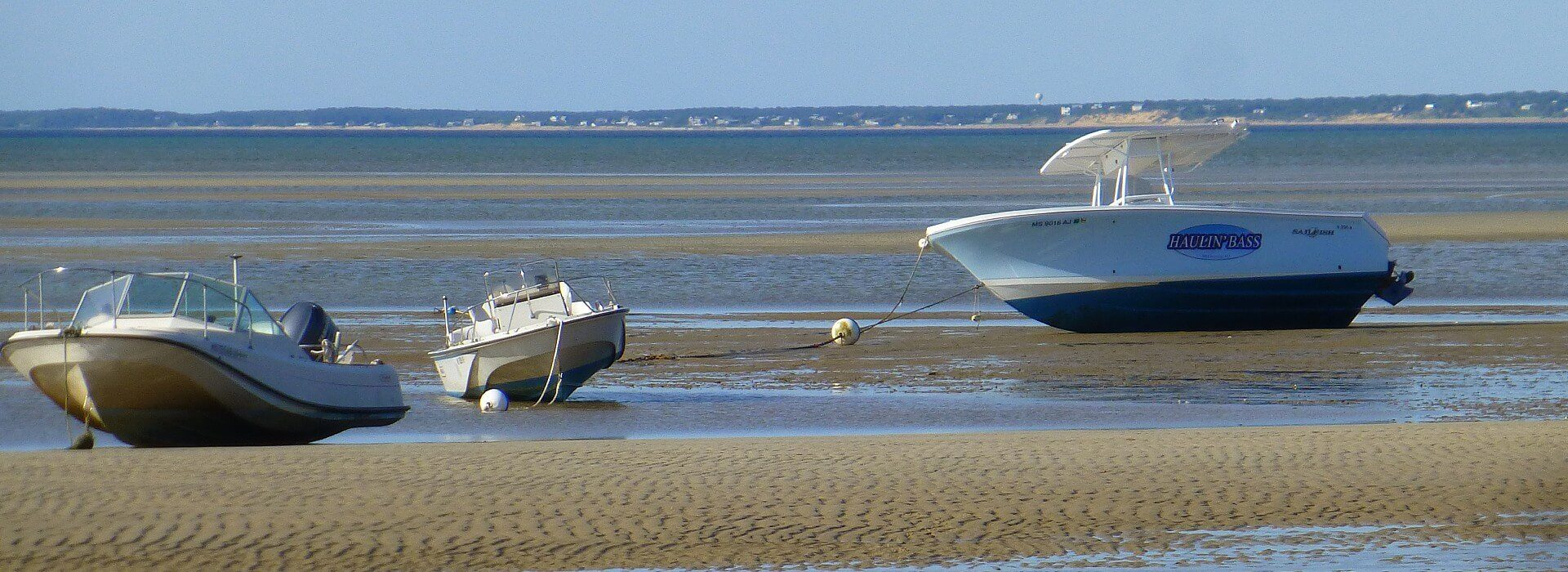 Three boats moored on the beach at waters edge with tide gone out and blue skies overhead