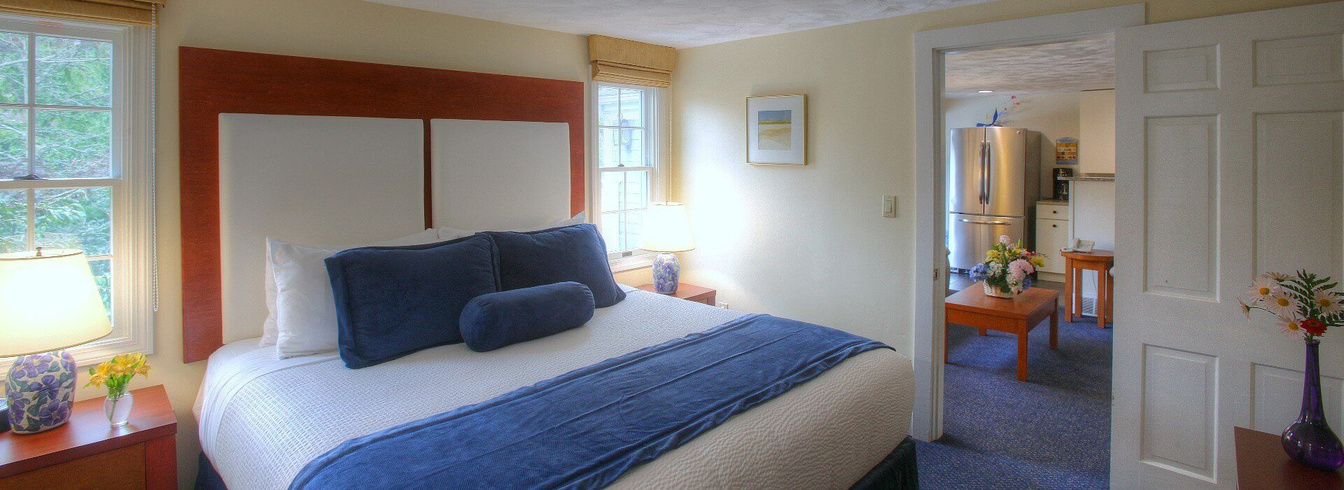 Large cottage bedroom with king bed, side tables under bright windows and doorway into sitting area and kitchenette