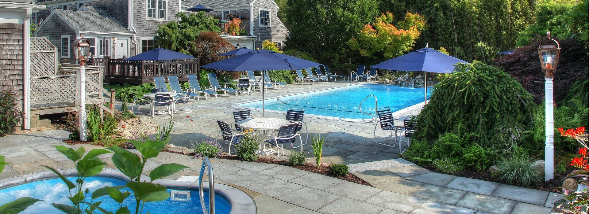 Expansive outdoor patio area with large pool lined with chairs, hot tub, and patio tables with blue umbrellas