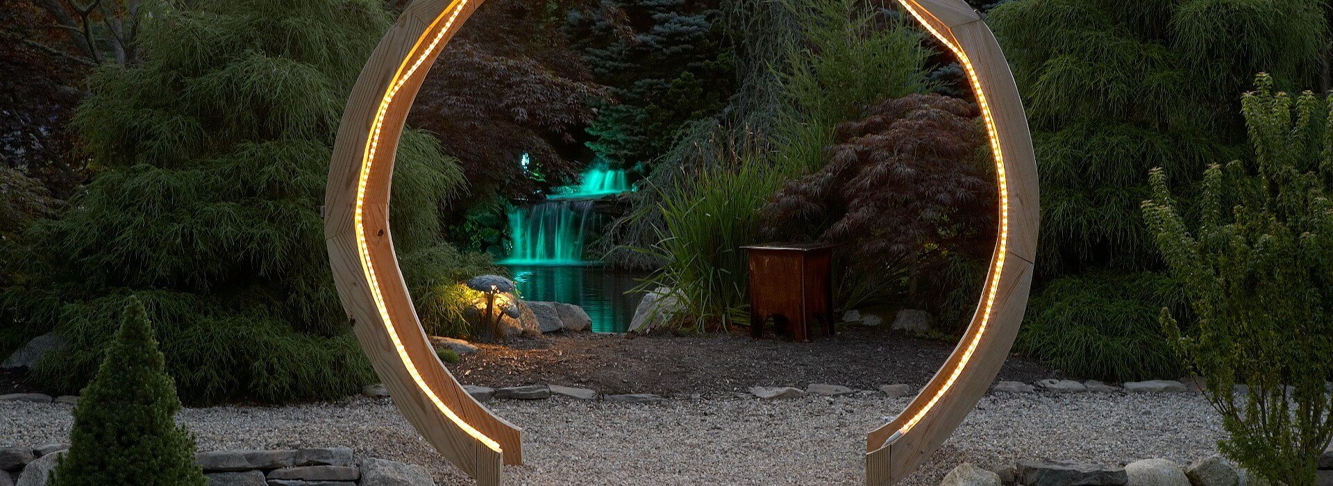 Beautiful wooden circular gate arch lit up by a rope light with view of a waterfall in the background